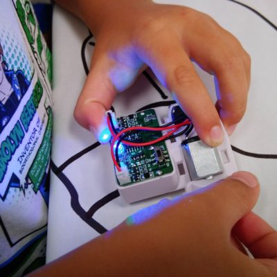 Student tinkers with their OptiBot.